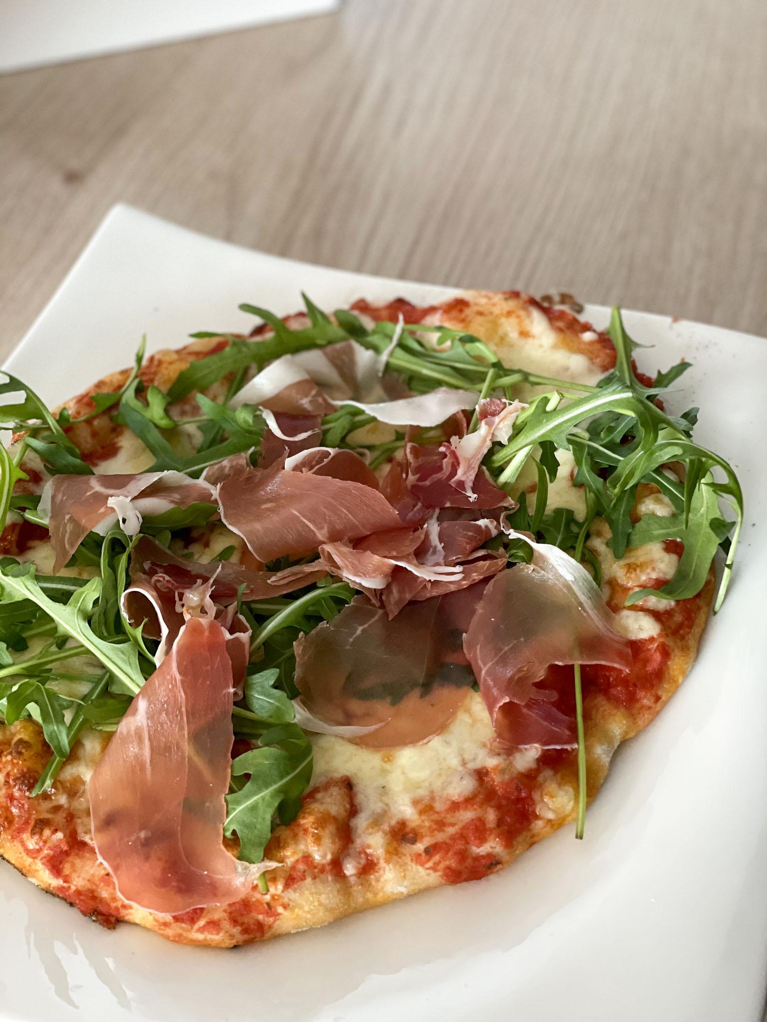 Värskelt ahjust tulnud isetehtud pizza rucola, mozzarella ja singiga
