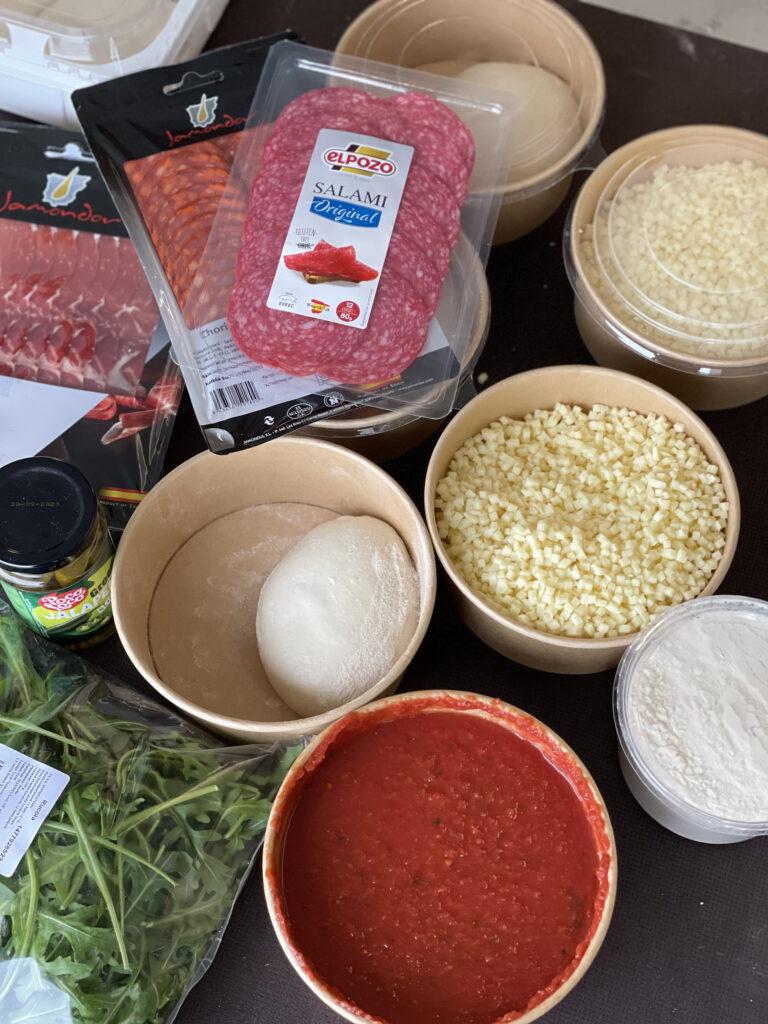 Pitsa valmistamise komponendid - juust, tomatipasta, salaami, sink, rucola